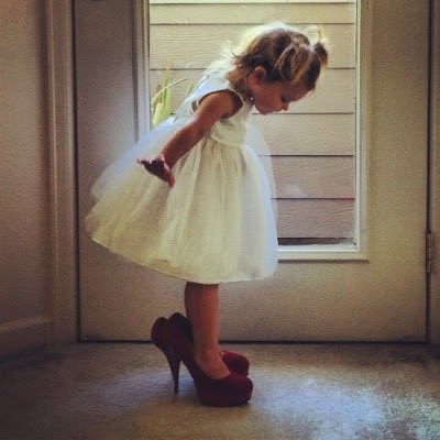Cute picture of flower girl in the bride's shoes.   wedding bliss