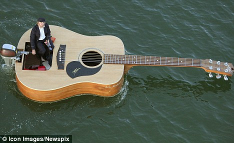Rockin' the boat: How a musician strummed through Sydney Harbour in his floating guitar | Mail Online