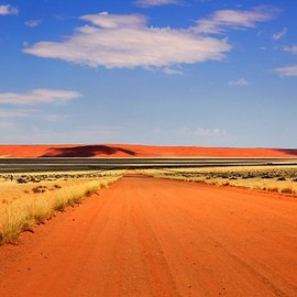 Africa | One of the never-ending straight long roads out in the remote countryside and farmland with sand dunes in distance, Naukluft National Park, Namibia |  © Jill Fisher