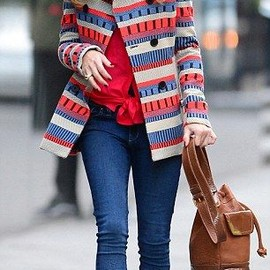 Olivia wore tight blue jeans and a red shirt underneath the hip-length wool coat