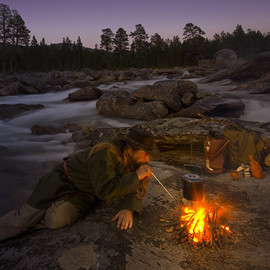 Using a blow poker to encourage a fire. Bushcraft camp in Northern Norway