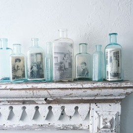 love the photos tucked into old blue bottles on a mantel