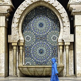 Morocco - Woman walking in front of Moroccan architecture in Casablanca.