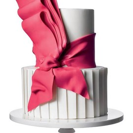 White wedding cake with big, hot pink bow