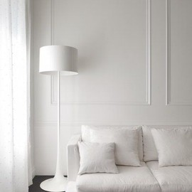 Luxuriate in the Living Room. White walls, dark floors, and boiserie wall moulding.