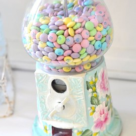 Pastel gumball candy machine filled with pastel M candies.