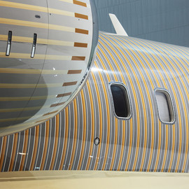 happy design studio wraps private jet in gradient stripe pattern