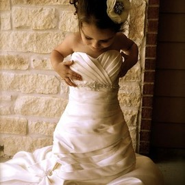 A flower girl wearing a wedding dress.