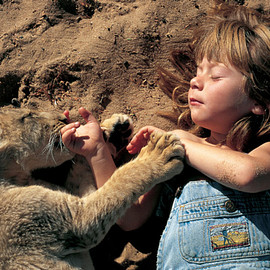 6-year-old Tippi Degre soaking up the sun with her pet lion cub, 1996