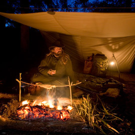 Providing shelter while still open to the night, a tarp is well suited to bushcraft use.