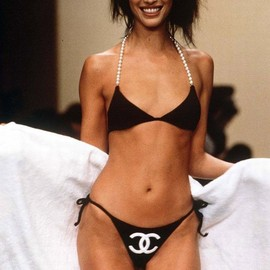 CHANEL - Christy Turlington model on catwalk wearing Chanel black bikini pearls and a white robe