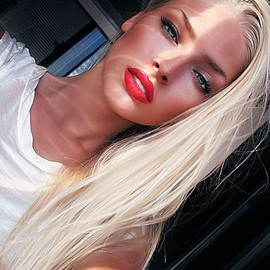 blonde hair, red lips, and a tan