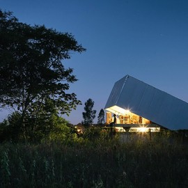 .Designed by Javier Corvalan - La Caja Obscura, a small home in Asunción, Paraguay featuring a tilting steel roof