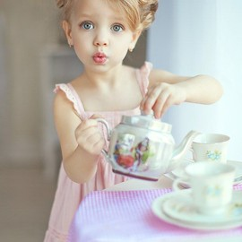 Little girl in pink dress having a tea party