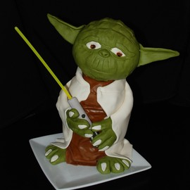 "This is a Yoda cake I made for my neighbor boy's 7th birthday.  It's a ""Wildberry"" cake with buttercream frosting and marshmallow fondant.  Rice crispy treats were used to make the head and shoulders, while the face/hands/ears are all formed from the marshmallow fondant. The base of the lightsaber is made of gumpaste, and the light part of the light saber is a glowstick.  I know he would have made more sense in the Star Wars contest, but I just found this site--and the cake is from last weekend!"