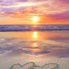 romantic beach sunset with hearts drawn in the sand