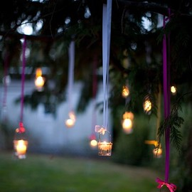 votives hanging by ribbons from a tree