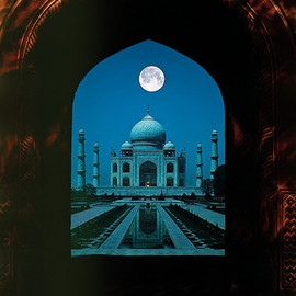 Agra, India - The full moon hangs above the enchanting Taj Mahal.