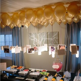 Photos hanging from balloons to create a chandelier over a table. - Photos hanging from balloons to create a chandelier over a table.