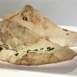 """Henny Burnett - Last Map, 2011 - 2012 """"Last Map"""" investigates shoe lasts as three dimensional maps; the making of a last involves the mapping of the individual contours of the foot. Fragments of ordinance survey maps and contour lines are printed and sewn onto muslin and reference memories of walks and travels. Small pressed foliage is incorporated into the folds of the map, such memorabilia that has been gathered by walkers across the centuries.  33cm x 90cm x 33cm  muslin, size, print,thread,foliage and light box"""